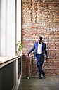 Businessman with longboard at brick wall by the window - HAPF02367