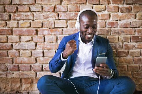 Happy businessman with headphones and smartphone cheering - HAPF02370