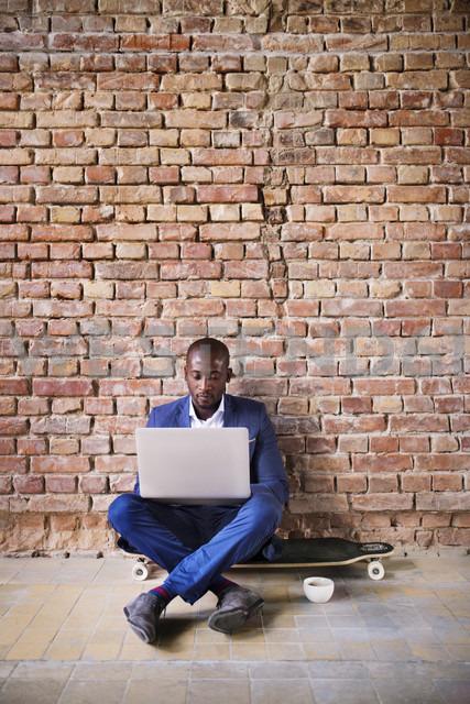 Businessman sitting on longboard at brick wall using laptop - HAPF02373