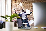 Carefree businessman in office throwing away papers - HAPF02379