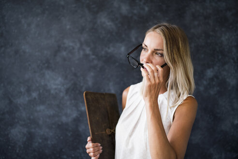 Woman with glasses holding wooden board - HAPF02382