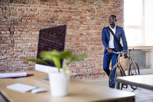 Businessman pushing bicycle in office - HAPF02391