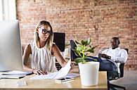 Businesswoman working at desk in office with colleague in background - HAPF02400