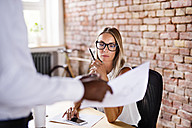 Colleague showing paper to serious woman at desk in office - HAPF02406