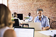 Portrait of confident businessman in office with colleagues in background - HAPF02418