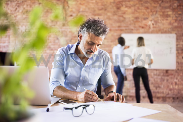 Businessman working in office with colleagues in background - HAPF02427