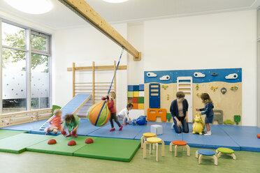 Pre-school teacher and children in gym room in kindergarten - MFF04048