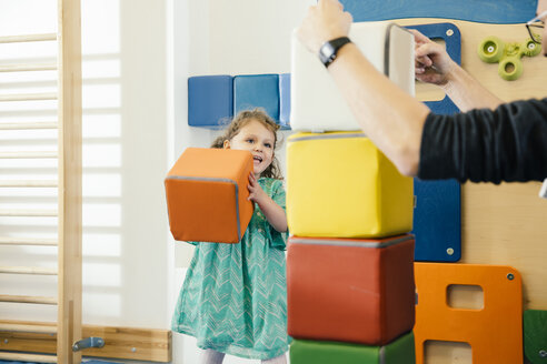 Happy little girl lifting up a soft building block in gym room of a kindergarten - MFF04057