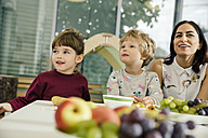 Children and teacher sitting at table with fruit in kindergarten - MFF04072