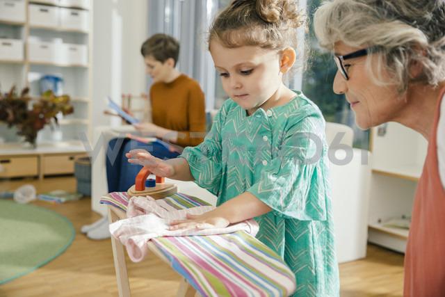 Teacher watching girl ironing in kindergarten - MFF04075