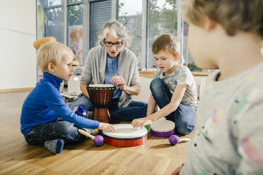 Children using percussion instruments with instructor in music room of a kindergarten - MFF04081