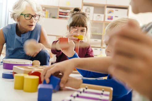 Children and teacher playing with musical instruments and toys in kindergarten - MFF04090