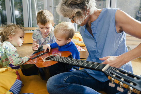 Pre-school teacher showing a guitar to children in kindergarten - MFF04096
