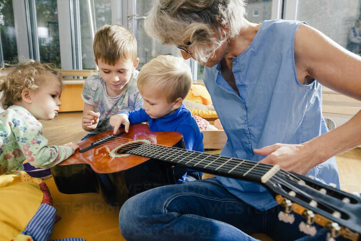 Pre-school teacher showing a guitar to children in kindergarten - MFF04096 - Mareen Fischinger/Westend61