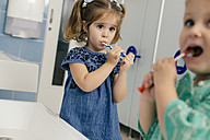 Little girls brushing their teeth in bathroom of a kindergarten - MFF04099