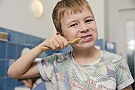 Portrait of boy brushing his teeth in bathroom of a kindergarten - MFF04105