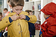 Boy putting on his raincoat in kindergarten - MFF04108