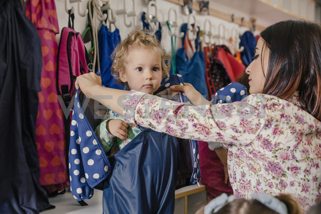 Pre-school teacher helping girl putting on mud pants in kindergarten - MFF04111
