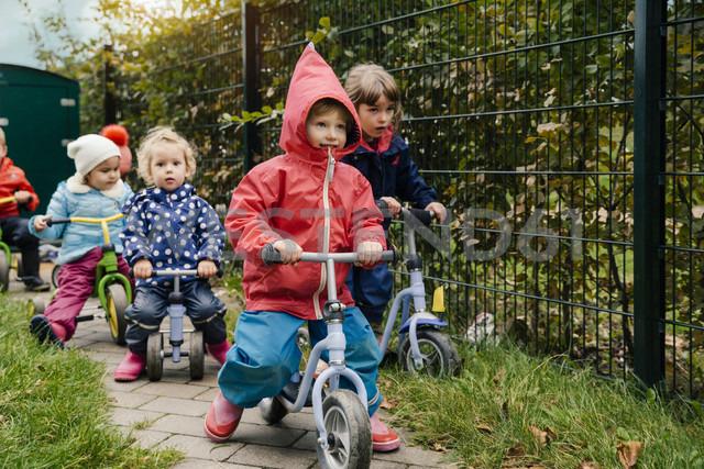 Children using scooters in garden of a kindergarten - MFF04114 - Mareen Fischinger/Westend61