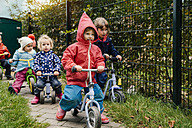 Children using scooters in garden of a kindergarten - MFF04114