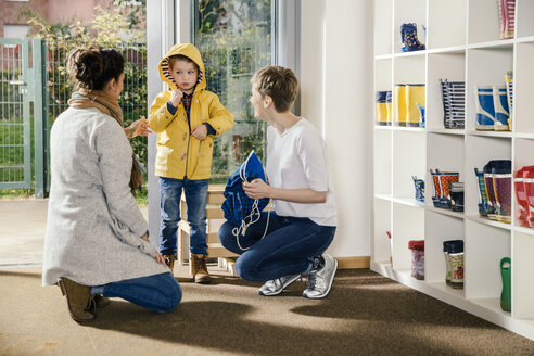 Boy in raincoat with mother and pre-school teacher in kindergarten - MFF04117
