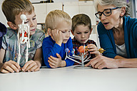 Pre-school teacher explaining solar system model to boys in kindergarten - MFF04126
