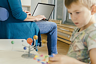 Boy exploring solar system model with woman with laptop in kindergarten - MFF04132