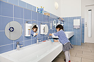 Little girl using water for brushing her teeth in bathroom of a kindergarten - MFF04144
