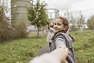 Portrait of smiling girl holding hands outdoors - KMKF00050