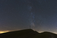Italy, Marche, silhouette of summit cross on Monte Catria at night - LOMF00662