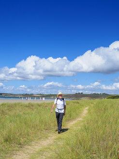 France, Bretagne, Active senior hiking on the beach of Treguer - LAF01931
