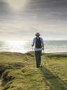 France, Bretagne, Active senior hiking on the beach of Treguer at sunset - LAF01937