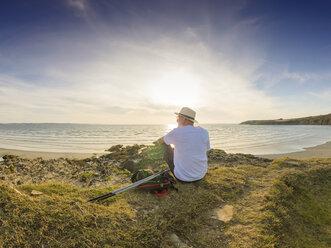France, Bretagne, Senior man taking a break on the beach, sitting on a dune - LAF01940