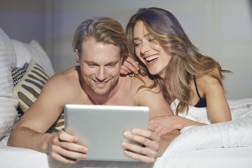 Portrait of relaxed couple with tablet lying on bed - PNEF00250