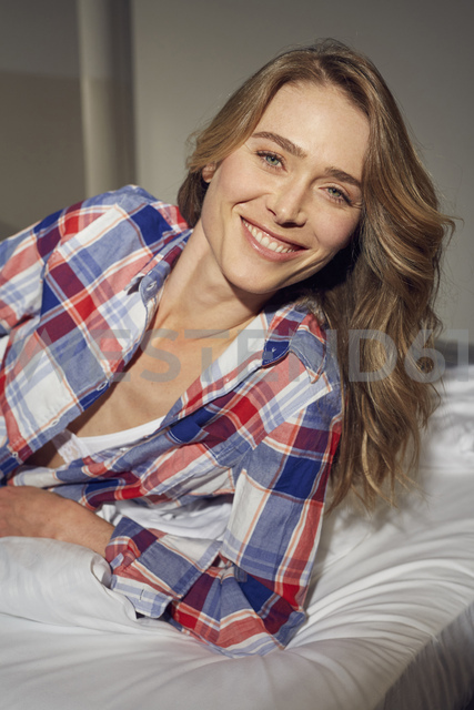 Portrait of laughing woman lying on bed - PNEF00253
