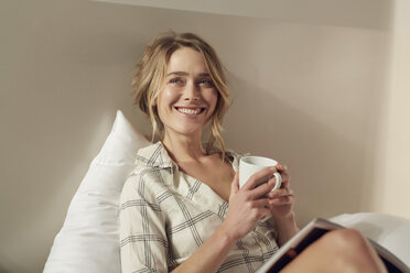 Portrait of happy woman sitting on bed with coffee mug and magazine - PNEF00262