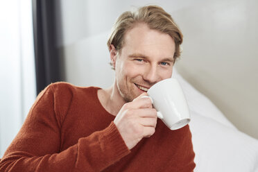 Portrait of smiling young man with coffee mug - PNEF00265
