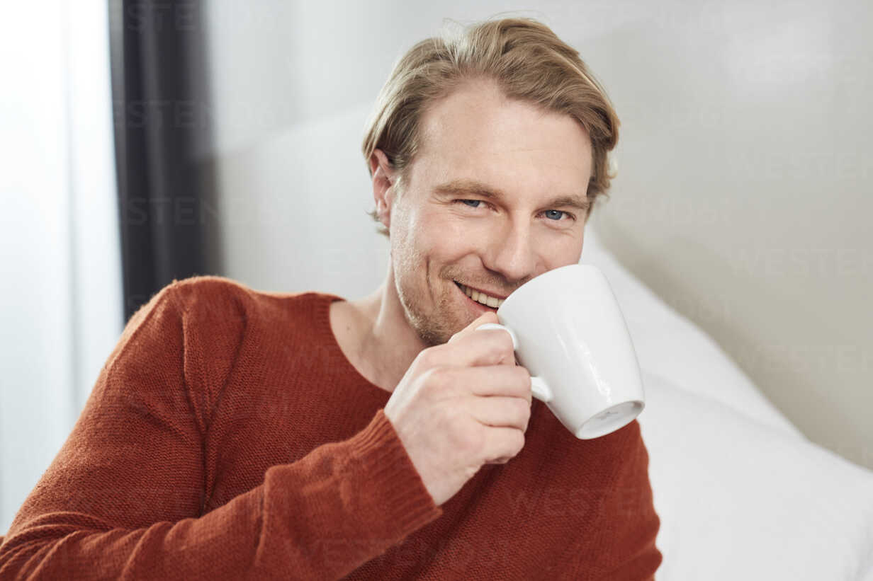 Portrait of smiling young man with coffee mug - PNEF00265 - Philipp Nemenz/Westend61