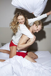 Couple having a pillow fight in bed - PNEF00271