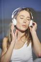 Portrait of woman behind windowpane listening music with headphones - PNEF00277