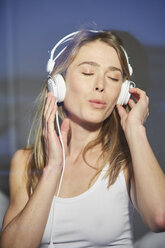 Portrait of woman behind windowpane listening music with headphones - PNEF00277