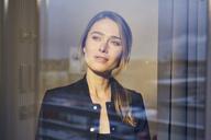 Portrait of businesswoman behind windowpane - PNEF00280