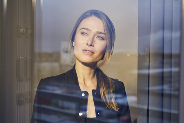 Portrait of businesswoman behind windowpane - PNEF00280