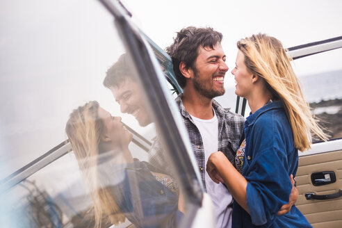 Spain, Tenerife, young couple in love on holidays with a van near the sea - SIPF01841