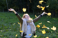 Happy teenage girl throwing up autumn leaves - LBF01698