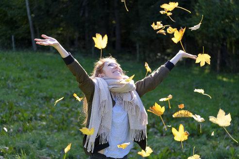 Happy teenage girl throwing up autumn leaves - LBF01698
