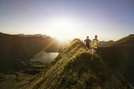 Germany, Allgaeu Alps, man and woman running on mountain ridge - MALF00012