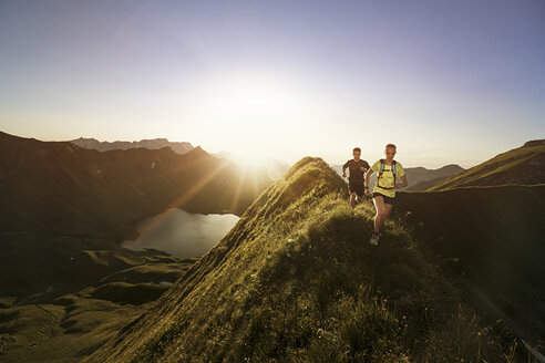 Germany, Allgaeu Alps, man and woman running on mountain ridge - MALF00012