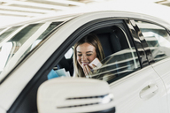 Smiling young woman with cell phone in car - UUF12203