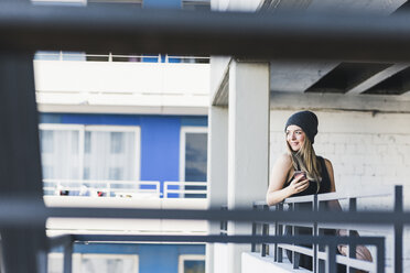 Smiling young woman with cell phone wearing wooly hat - UUF12215